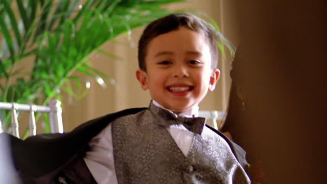 Slow motion medium shot small Hispanic boy in tuxedo dancing / turning away