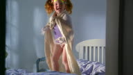 Slow motion medium shot small redhead girl jumping on bed
