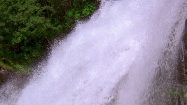 Slow motion medium shot tilt down pan waterfall turning into rapids with trees and mountains in background / Norway