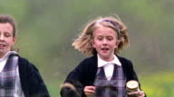 Slow motion medium shot tilt down tilt up rack focus two girls in school uniforms with butterfly net and jar run in grass toward cam / MO