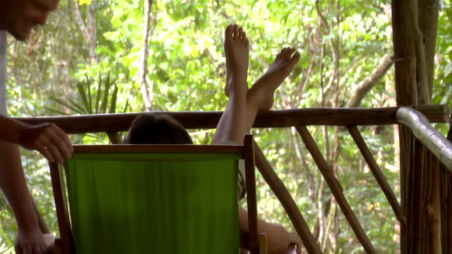 Slow motion medium shot tilt down woman sitting in chair on deck of ecolodge with feet up/ The Amazon, Brazil