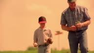 Slow motion medium shot tilt up male farmer kneeling and examining crops / boy playing with baseball mitt behind him / Iowa