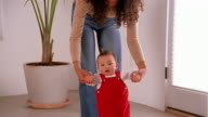 Slow motion medium shot tilt up mother guiding baby taking first steps