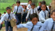 Slow motion medium shot tracking shot large group of small schoolchildren walking and running to school / Nepal
