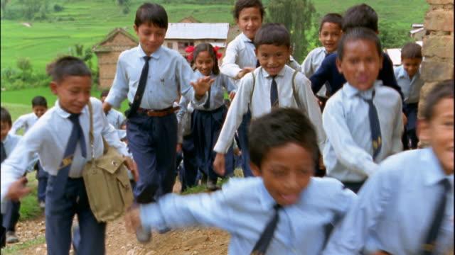 Slow motion medium shot tracking shot large group of small schoolchildren walking and running to school / Nepal