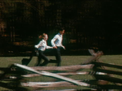 1970 slow motion medium shot tracking shot young couple holding hands and running through field with wooden fence in foreground
