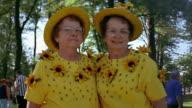 Slow motion medium shot twin mature women wearing identical yellow outfits posing outdoors