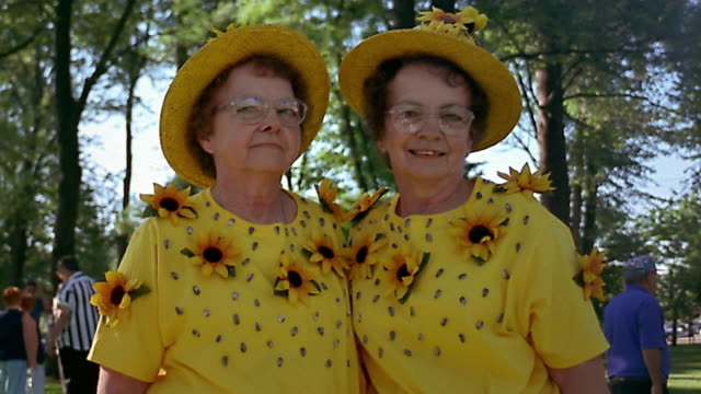 Slow motion medium shot twin mature women wearing identical yellow outfits posing outdoors