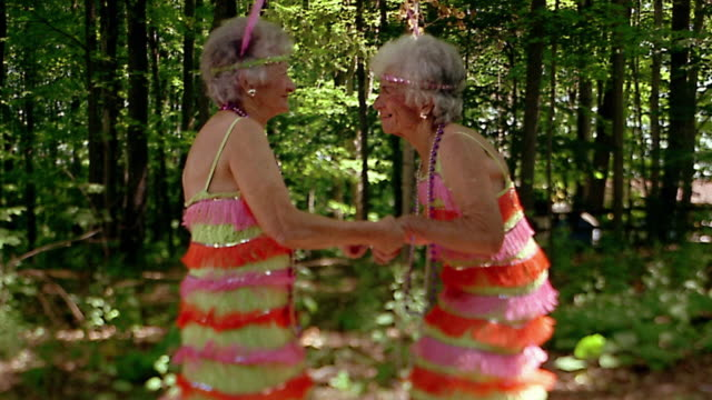 Slow motion medium shot twin senior women in flapper costumes dancing together / forest in background