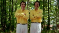 Slow motion medium shot twins wearing identical yellow shirts and white pants / crossing their arms / forest in background