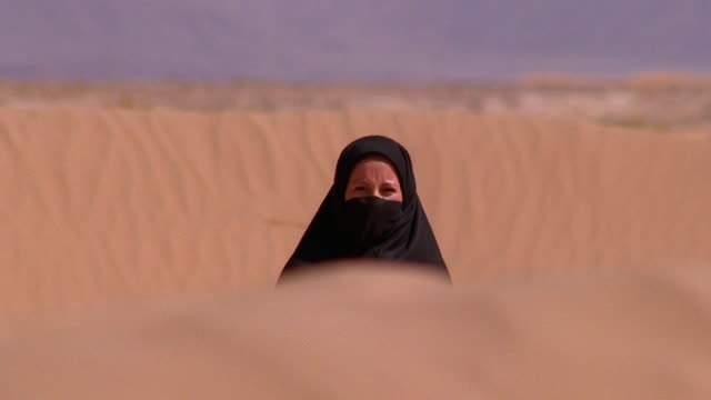 Slow motion medium shot woman in black nikab with headscarf and veil walking in dunes in desert / Morocco