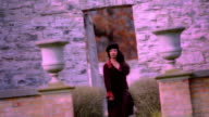 Slow motion medium shot woman walking through doorway in wall and towards camera