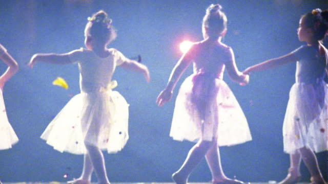 Slow motion medium shot young ballerinas in tutus walking in line / holding skirts and bowing w/confetti falling