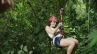 Slow motion medium tracking shot of woman ziplining in rain forest / Quepos, Puntarenas, Costa Rica