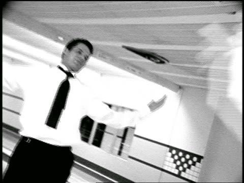 B/W slow motion men in formalwear in goofing around in bowling alley