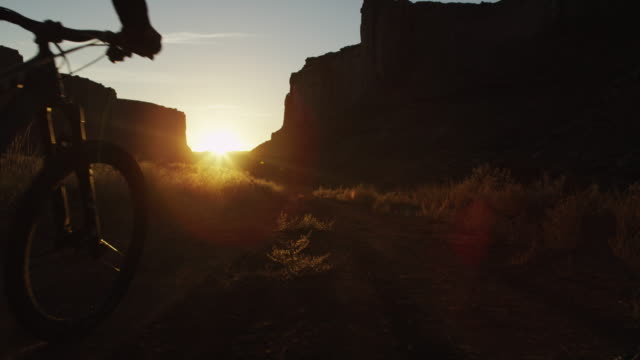 Slow motion, mountain bikers in scenic landscape at sunset