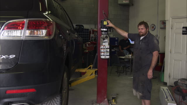 Slow motion of a scruffy mechanic in a garage.