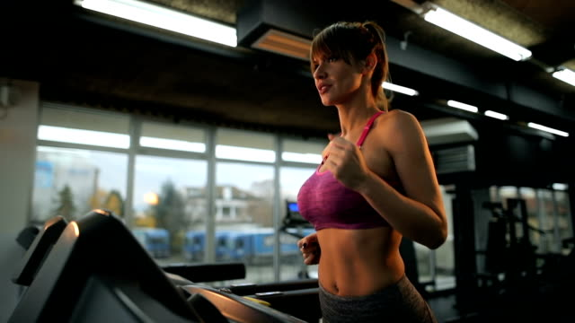Slow motion of athletic woman running on a treadmill in health club.