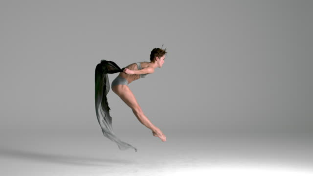 slow motion of ballerina jumping with silk fabric