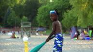 Slow Motion of boy playing baseball at beach