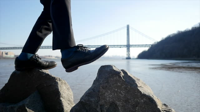 Slow Motion of Close-Up of a Man's Feet Walking over Rocks at Water's Edge. Bridge in the Background. Symbolizing Independence, Freedom and Liberty.