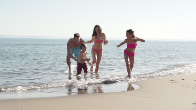 Slow motion of family running out of the sea.