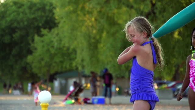 Slow Motion of Girl playing baseball at beach