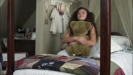 Slow motion of girl playing with bear.