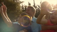 Slow motion of grandchildren and grandparents in garden playing with bubbles.