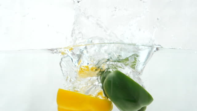 Slow Motion Of Green, Yellow Bell Pepper Drop In The Water
