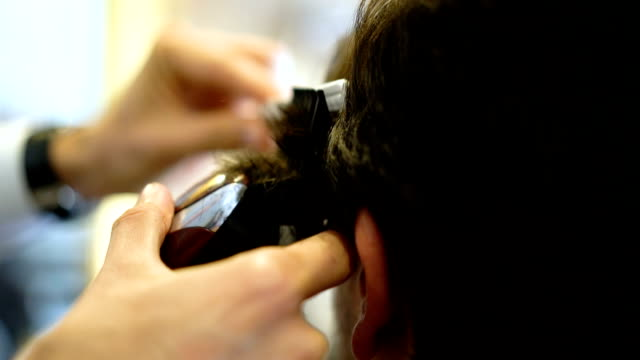 Slow motion of hair dresser cutting the hair of a customer with an electric razor