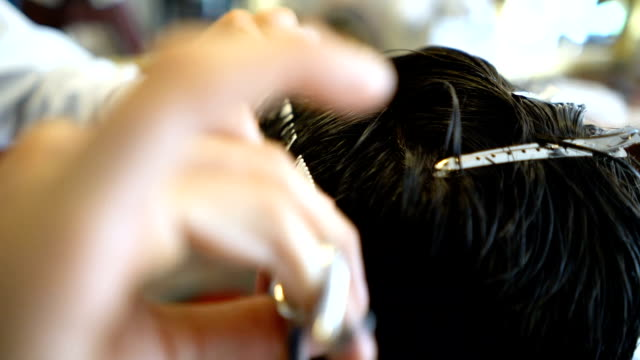 Slow motion of hair dresser cutting with scissors and using a comb