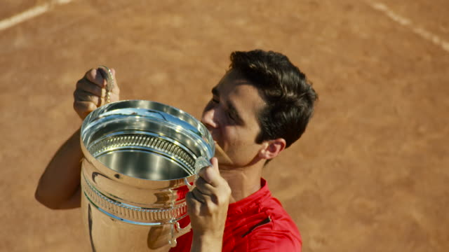 Slow motion of man kissing tennis trophy on clay court