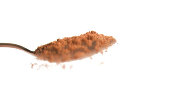 Slow motion of nutmeg powder being poured