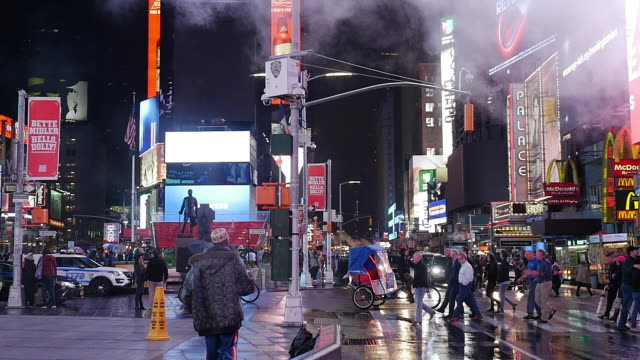 Slow motion of people and traffic in Times Square, New York City at a rainy night