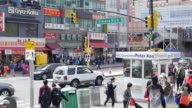 Slow motion of people walking and shopping in Flushing, Queens, New York