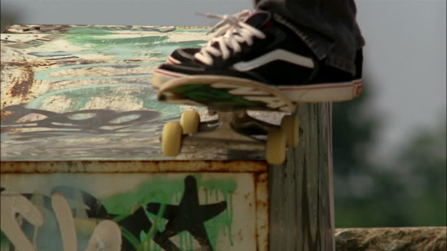 Slow motion of skater grinding on metal covering bombed with graffiti