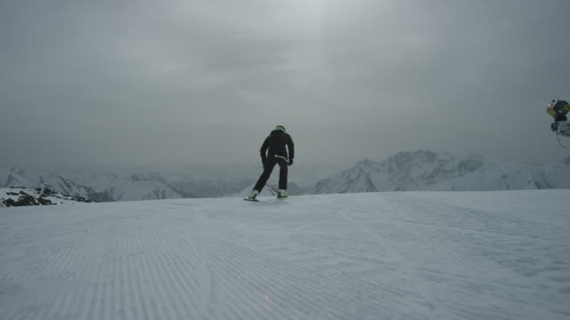 Slow motion of skier first standing and then skiing downhill.