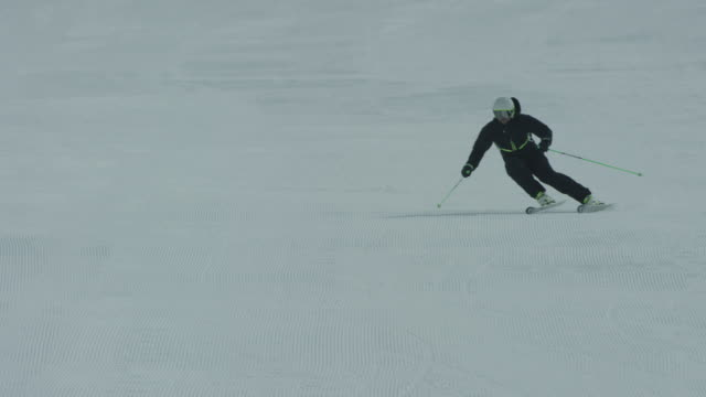 Slow motion of skier skiing down snowy slope.