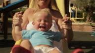 Slow motion of toddler and his mother on slide/Benhavis, Marbella region, Spain