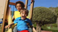 Slow motion of two children on slide in park.