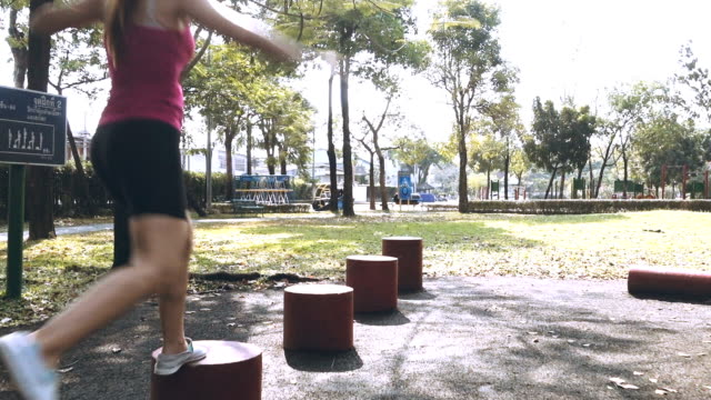 Slow Motion Of Woman Jumping On The Red Block Shape In Public Park