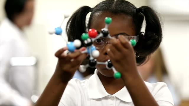 Slow motion of young girl studying model in science class