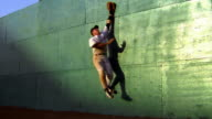 slow motion outfielder jumping + missing baseball against green wall / he falls on ground