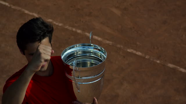Slow motion overhead of man on clay tennis court waving while holding tennis trophy