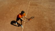 Slow motion overhead of man playing tennis on clay court