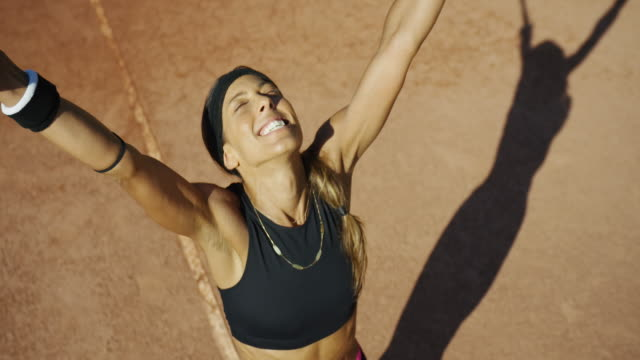 Slow motion overhead shot of woman raising her arms in victory on clay tennis court with long shadow