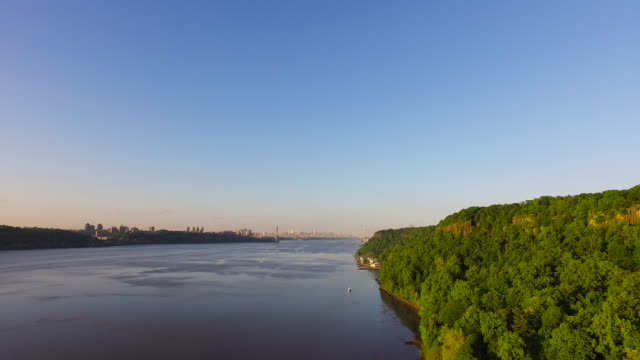 Slow motion pan from behind tree covered hill to wide view of Hudson River