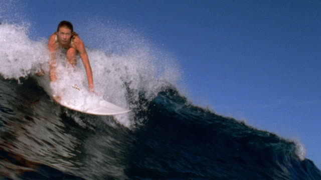 Slow motion pan medium shot female surfer standing up on surfboard and riding wave / Tahiti
