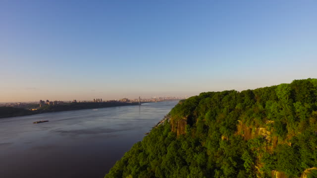 Slow motion pan over Hudson River, pulling away from George Washington Bridge over tree covered hill